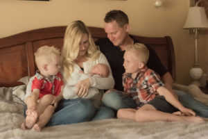family on bed with newborn son lifestyle session