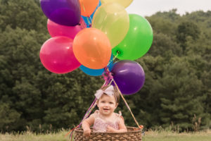 girl in basket with balloons 1st birthday styled session