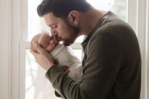 dad kissing newborn daughter's head in front of window lifestyle newborn session
