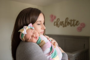mom holding newborn baby in nursery lifestyle session