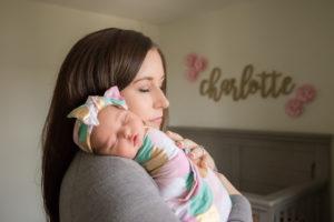 mom holding newborn baby in nursery lifestyle session