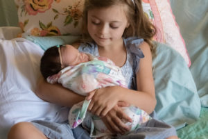 big sister holding new baby sister on hospital bed in fresh 48 session