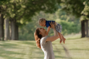 mom holding son in the air outdoors