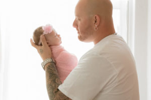dad looking at his newborn baby girl in front of window