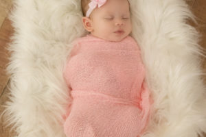 newborn baby girl in pink wrap and cream flokati