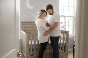 peeking in on mom and dad with newborn son in nursery