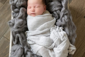 newborn baby boy in gray wrap in wooden crate