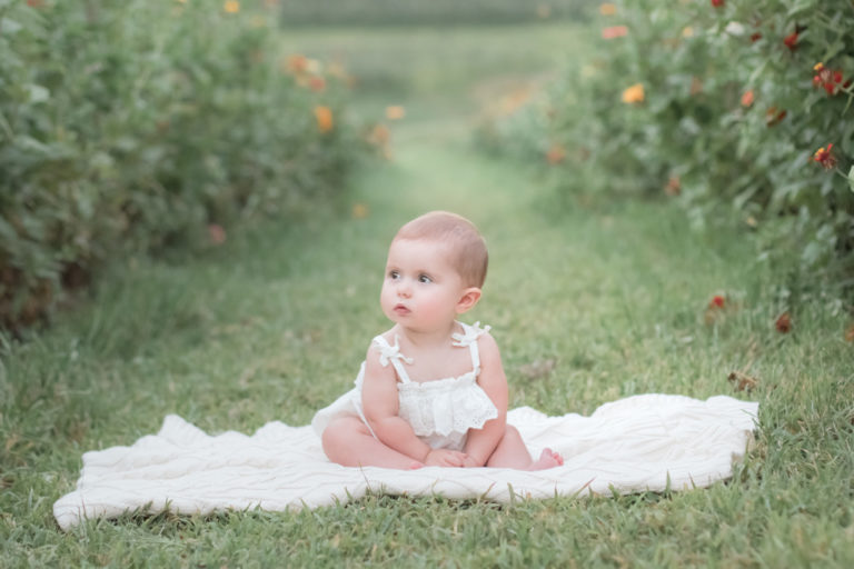 one year old girl in simmons flower field on cream blanket