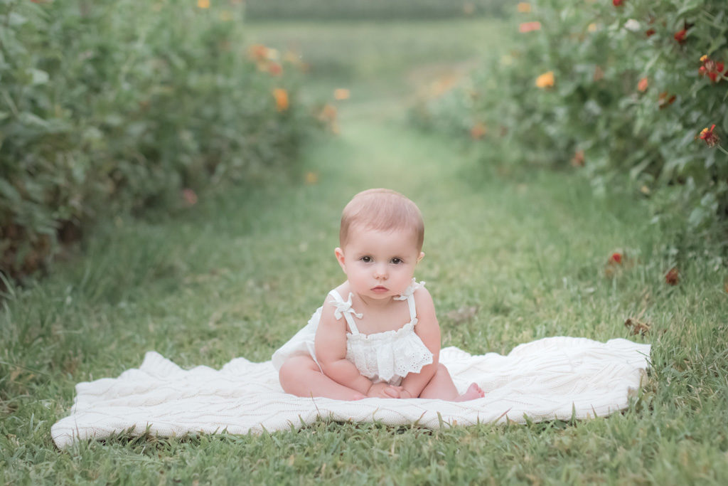 baby girl sitting on blanket in simmons farm flower field