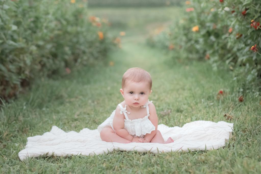 baby girl sitting on blanket in simmons farm flower field