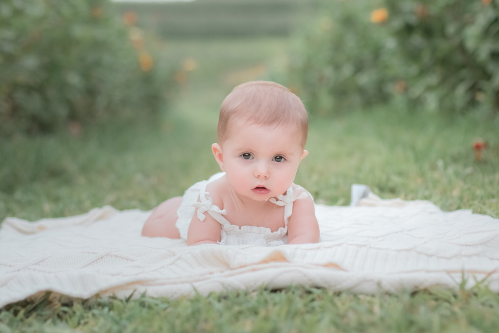 baby girl laying on cream blanket in simmons farm flower field