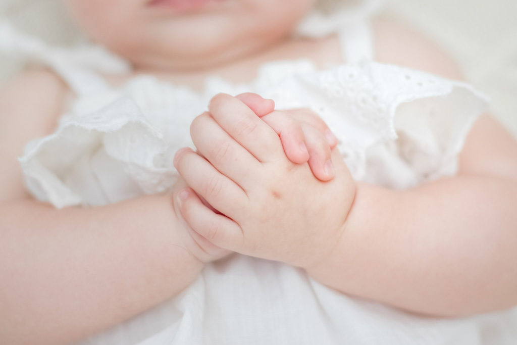 baby girl in simmons flower field with hands folded