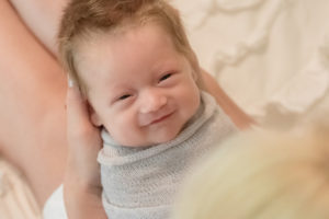 newborn boy smiling at his mother