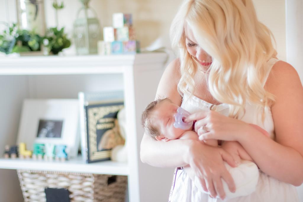 mother holding newborn son in nursery