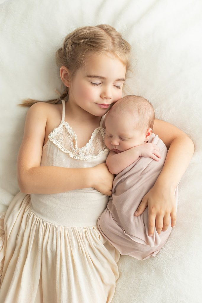 big sister holding newborn sister on bed_petite magnolia photography