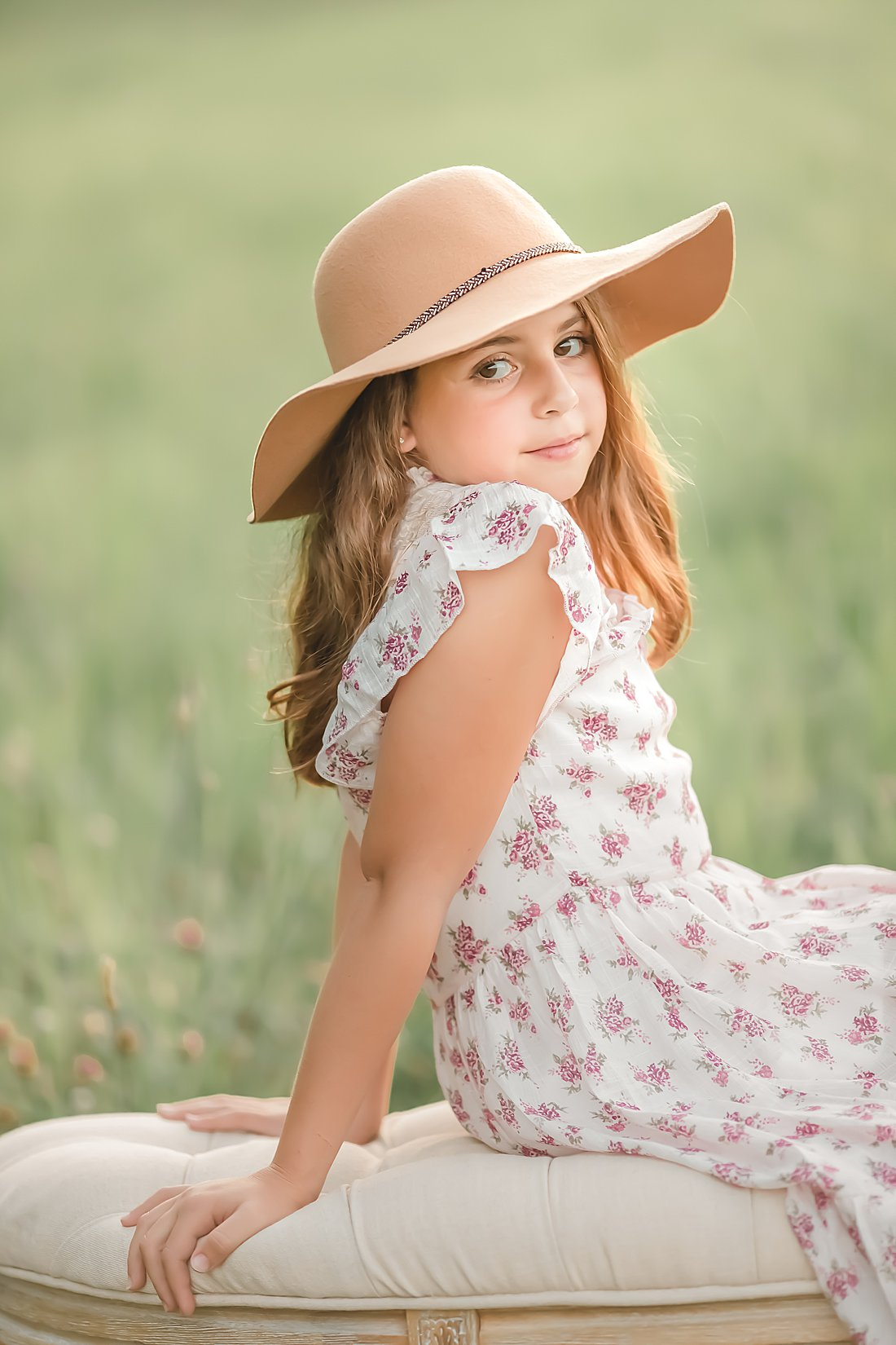 girl in floral dress and hat sitting on bench in field at sunset_petite magnolia photography