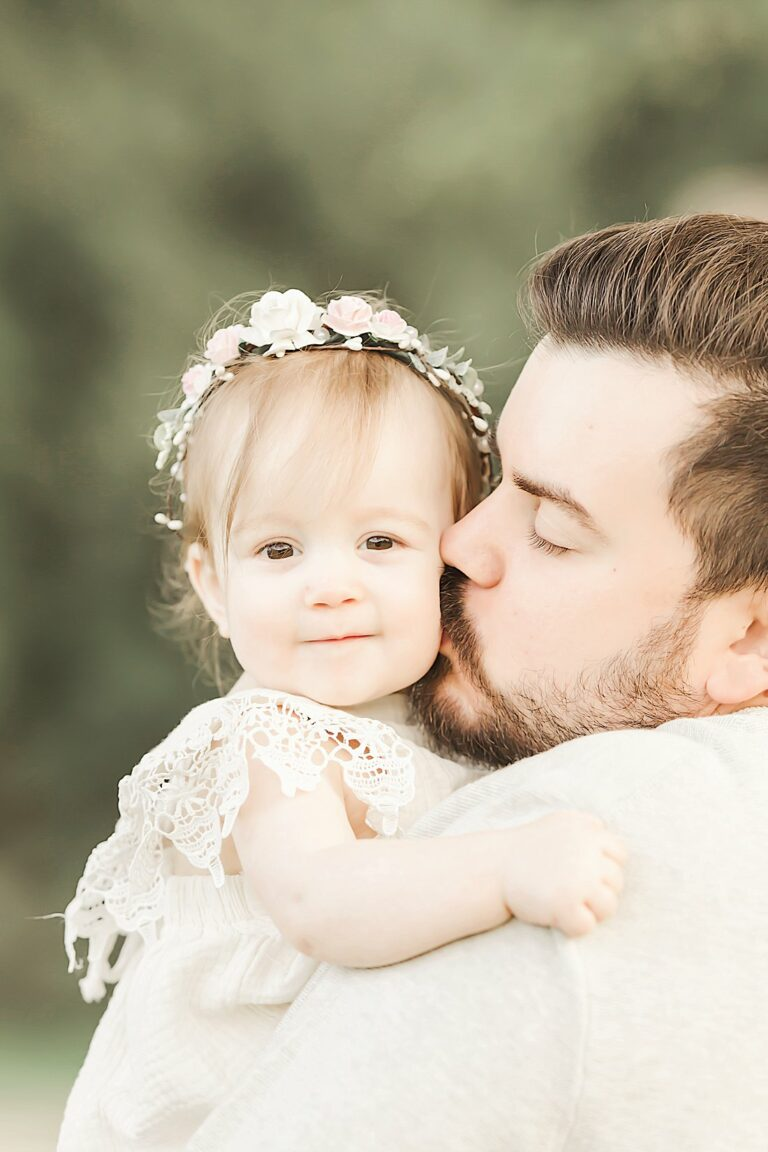 father kissing baby girl on cheek_petite magnolia photography