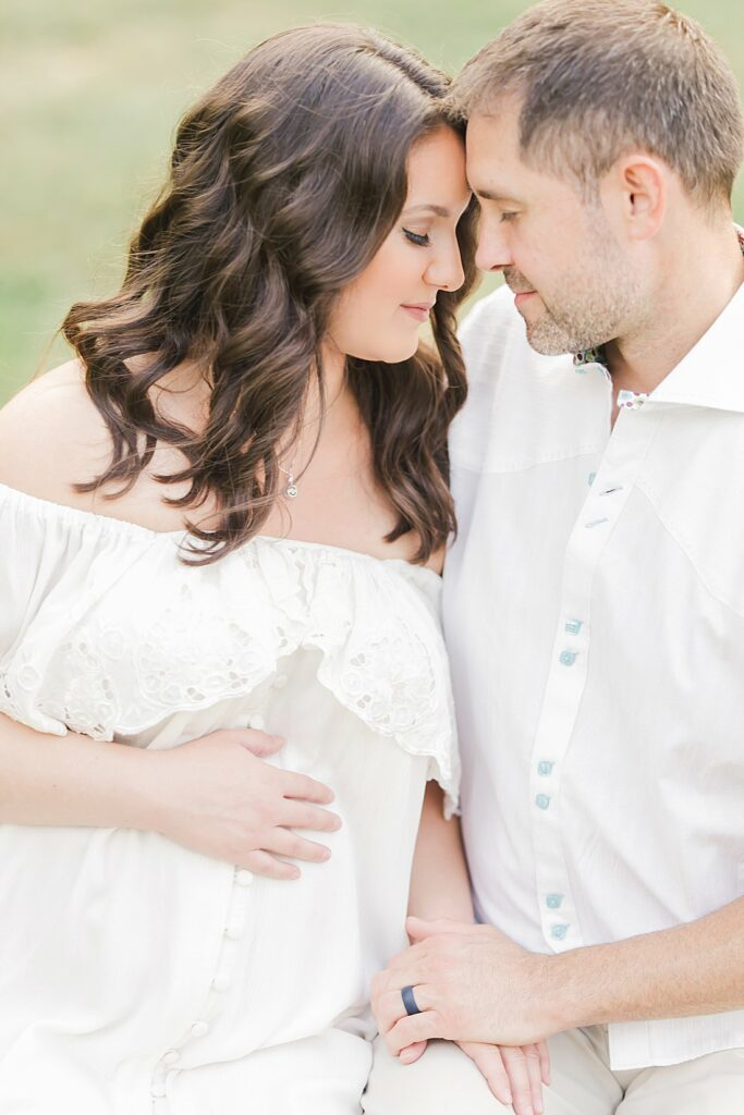 expectant parents holding each other close_petite magnolia photography